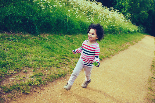 Child (3-4) Running Freely in Park 477446750