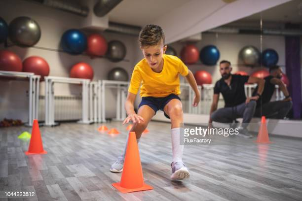 child running from a cone to cone during his warm up with a personal trainer - cone shape stock photos and pictures