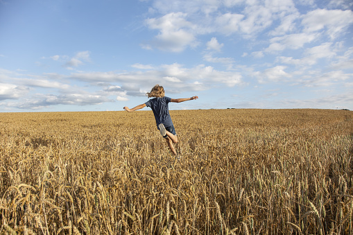 Child running in a field of wheat - gettyimageskorea
