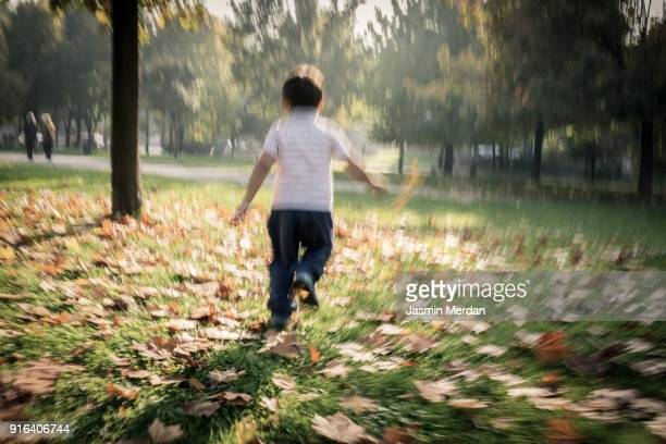 Child running in autumn park blurred motion
