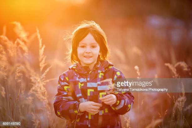 Child running in snowy forest. Toddler kid playing outdoors. Kids play in snow