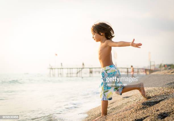 child running on beach - human limb stock pictures, royalty-free photos & images
