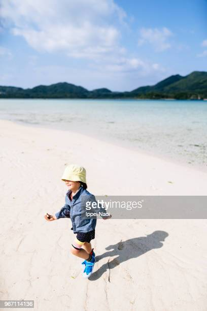 Child running on white sand beach, Okinawa, Japan