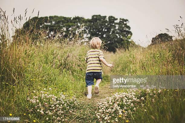 Child running through a field of tall grass