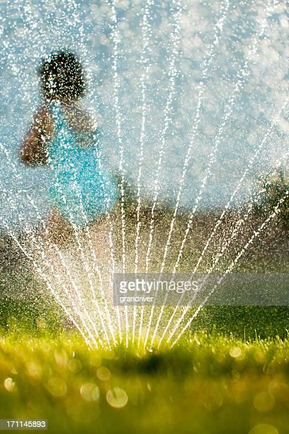 Child Running Through Sprinklers