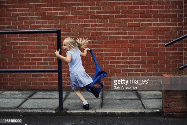 child running to school - schoolgirl stock pictures, royalty-free photos & images