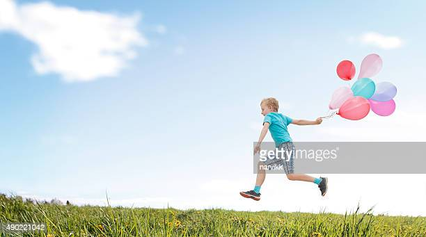 Child running with balloons over the meadow