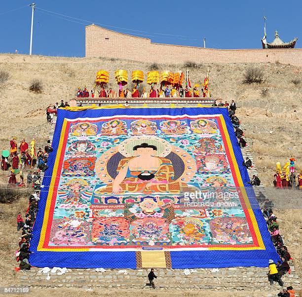 A child runs across a hillside path near the bottom of a momentarily unfurled Tibetan Buddhist thangka during the Sunning of the Buddha when a huge...