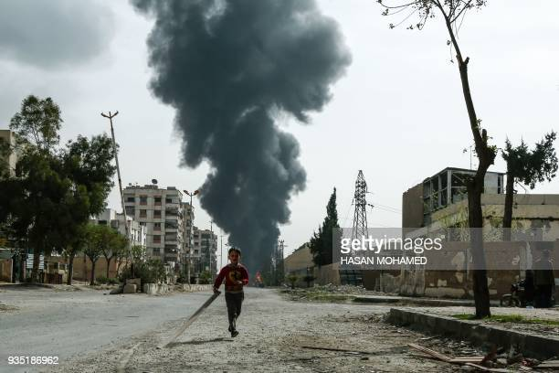 Child runs along a street in front of clouds of smoke billowing following a reported air strike on Douma, the main town of Syria's rebel enclave of...