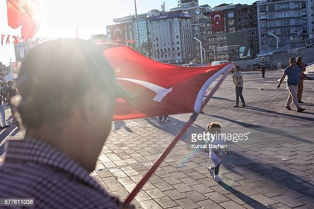 A child runs as a a Turkish man waves his flag at Istanbul's central Taksim Square on July 19 2016 in Istanbul Turkey Clean up operations are...