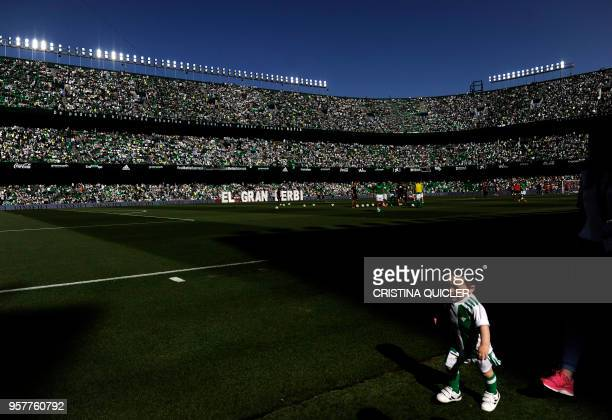 Child runs before the Spanish league football match between Real Betis and Sevilla at the Benito Villamarin stadium in Sevilla on May 12, 2018.
