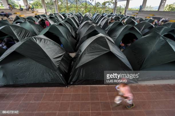 TOPSHOT A child runs beside a group of tents at a shelter in Mocoa Putumayo department southern Colombia on April 3 2017 Residents of Mocoa were...
