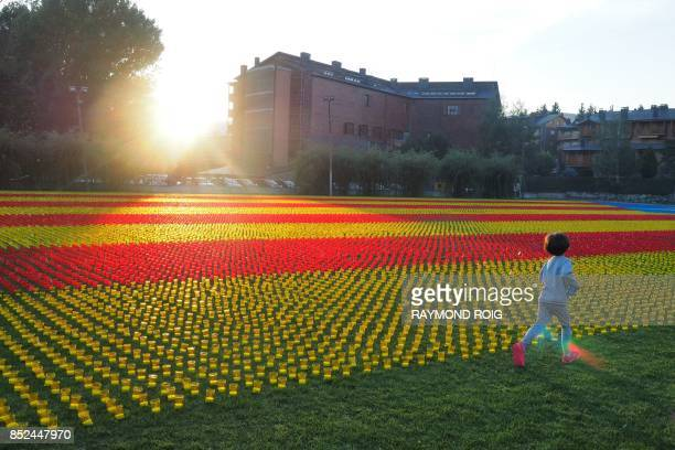 A child runs by a Catalonia's independantist flag made of 82000 candles in Llivia in the Spanish Pyrenees near the French and Andorran borders on...