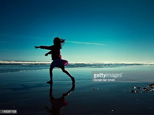 Child runs on beach