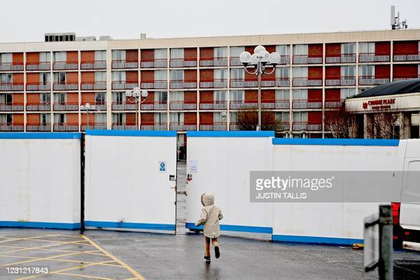 Child runs outside the gates of the Crowne Plaza hotel, which is housing asylum seekers as they wait for their asylum claims to be processed, at...