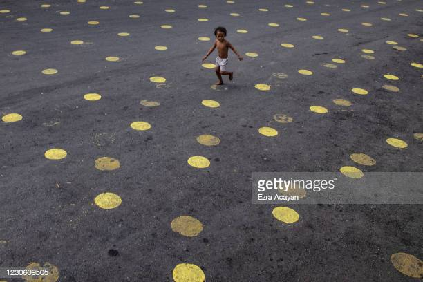 Child runs over social distancing markers on the road as part of preparations for masses a day before the Feast of Santo Nino on January 16, 2021 in...