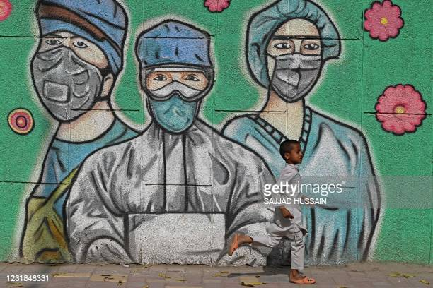 Child runs past a wall mural depicting frontline Covid-19 coronavirus warriors wearing face masks along a road in New Delhi on March 21, 2021.