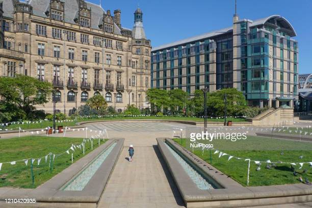 Child runs through a pathway in the Peace Gardens in Sheffield , on 19 April 2020.