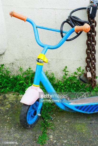 child s scooter chained to wall - lyn holly coorg stock photos and pictures
