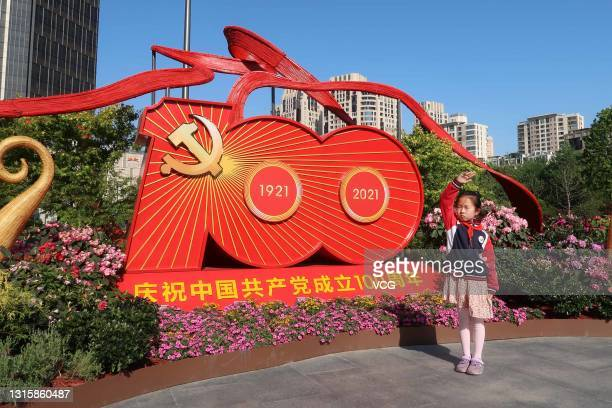 Child salutes in front of a sign at the site of the first National Congress of the Communist Party of China during its trial operation on May 1, 2021...