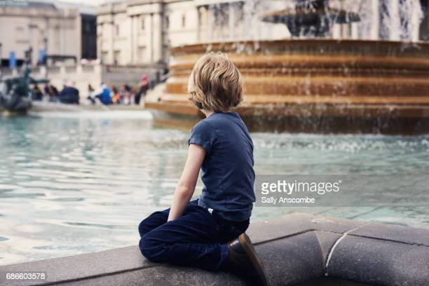 Child sat looking at a fountain