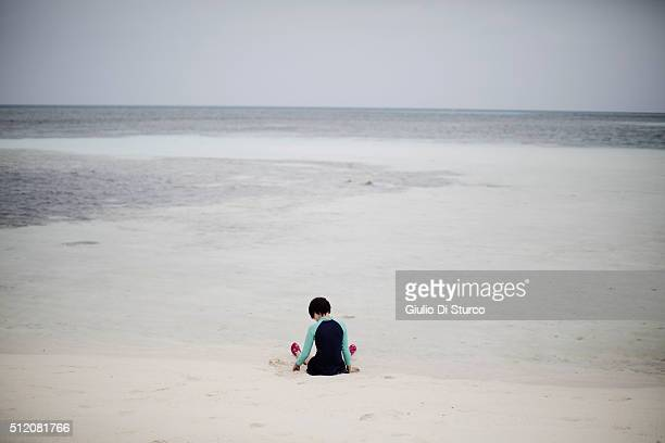 A child seating on the beach during late afternoon on February 02 2016 at Adaaran Select Hudhuranfushi Maldives China's top diplomats estimates...
