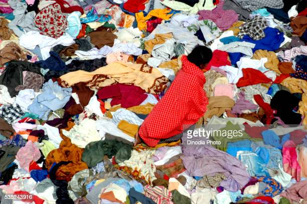 a child selecting from the stacks of clothes that arrived in nagapatinam following the tsunami disaster in nagapatinam, tamil nadu, india. - tamil nadu stock pictures, royalty-free photos & images