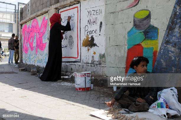 Child sells wood toothpick as he sits on a pavement as artists draw graffiti during an Open Day of graffiti campaign call for peace on March 15, 2018...