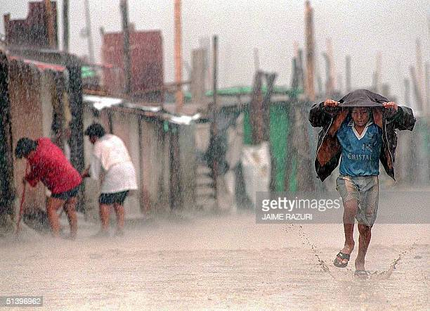 A child shields himself from torrential rains with his jacket as he runs through a flooded dirt street while local residents sweep mud and water out...