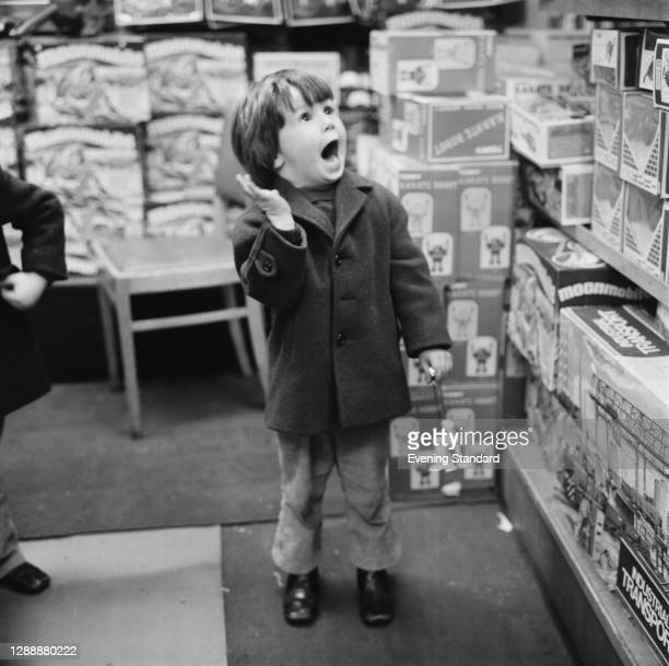Child shopping in Hamley's toy store on Regent Street at Christmas, UK, December 1971.