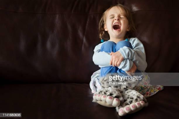 child shouting and wearing novelty monster feet slippers - ein mädchen allein stock-fotos und bilder