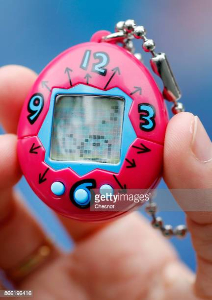 A child shows a 'Tamagotchi' electronic pet on October 25 2017 in Paris France Tamagotchi is a virtual electronic animal which means 'cute little...