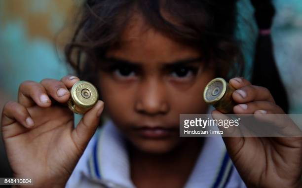 A child shows part of a mortar shell after a heavy mortar shelling by Pakistan Rangers on Saturday night at Arnia village on September 17 2017 in...