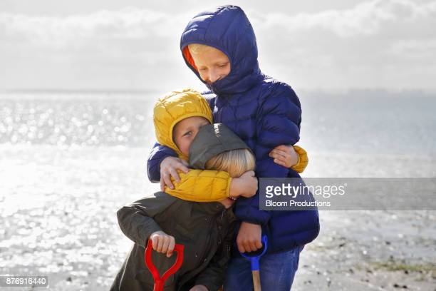 Child siblings hugging at the beach