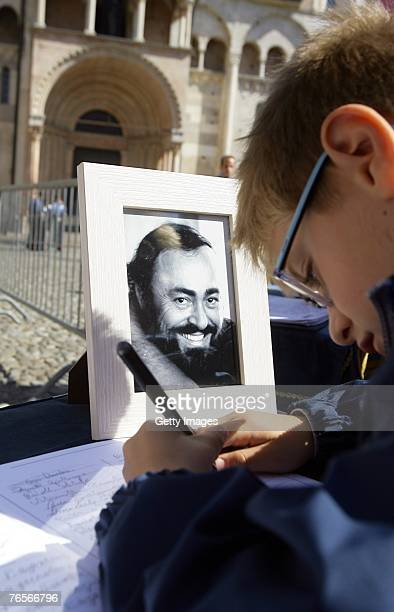 A child signs a book of condolence at the entrance of Modena's Duomo where the coffin of Maestro Luciano Pavarotti lies in state on September 07 2007...
