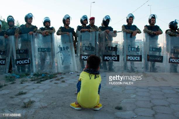 Child sits across Iraqi security forces standing guard as people demonstrate in the southern city of Basra on June 22 against corruption and lack of...