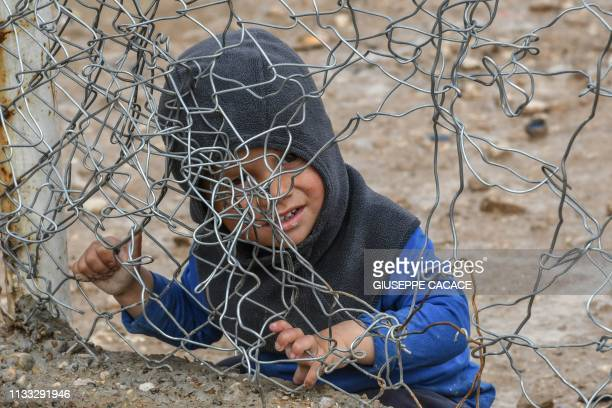 TOPSHOT A child sits behind a wire fence in alHol camp which houses relatives of Islamic State group members in alHasakeh governorate in northeastern...