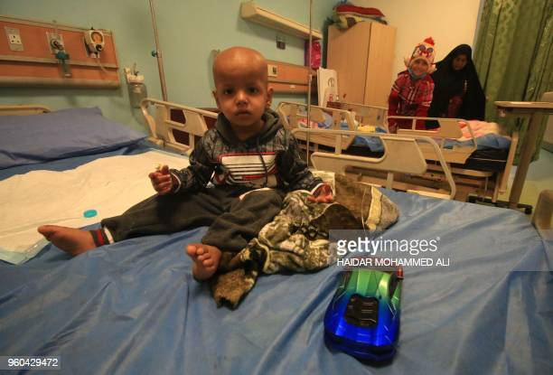 A child sits on a bed at the children's cancer hospital in the southern Iraqi city of Basra on December 19 2017