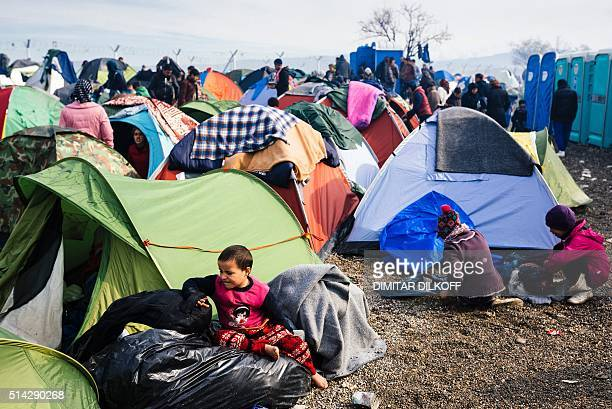 Child sits on a plastic bag in front of a tent at a makeshift camp at the Greek-Macedonian border near the Greek village of Idomeni where thousands...