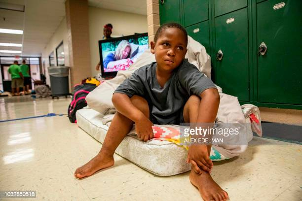 TOPSHOT A child sits on a single mattress at a Hurricane Florence evacuation shelter at Conway High School on September 13 2018 in Conway South...
