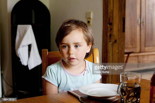 child sits on a table and looks nice and relaxed
