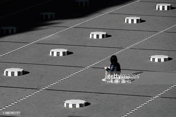 A child sits on one of the Colonnes de Buren an art installation by French artist Daniel Buren in the inner courtyard of the Palais Royal gardens in...