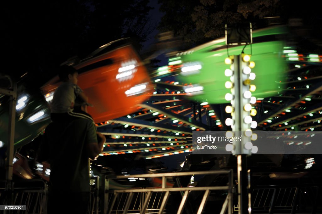 Child sits on the neck of a man as watch a ride a small community carnaval, in Wyndmoor, PA, just outside Philadelphia, on June 8, 2018.