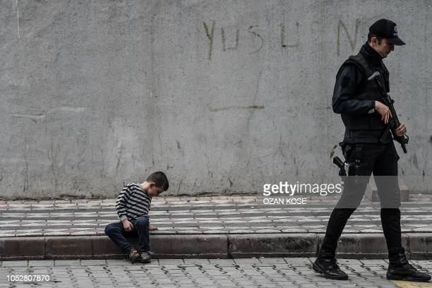 Child sits on the pavement as a Turkish police police officer walks past close to a cordoned off underground car park, in Istanbul on October 23,...