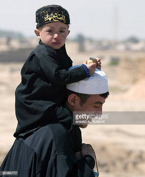 A child sits on the shoulders of his father as they and other Shiite Muslim pilgrims march towards the holy city of Karbala from southern Iraqi...