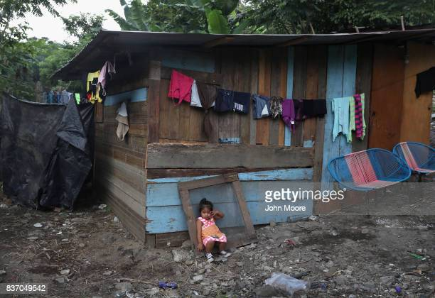 A child sits outside her family's oneroom home in an impoverished neighborhood on August 19 2017 in San Pedro Sula Honduras Honduras is consistently...