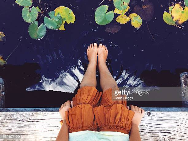 child sitting beside pond placing feet into water - low section stock pictures, royalty-free photos & images