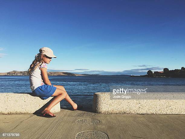 Child sitting beside the ocean in afternoon light