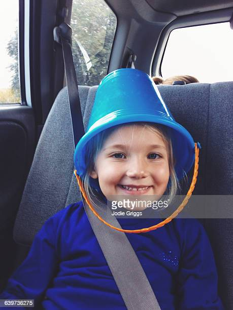 Child sitting in back of car with Bucket on Head