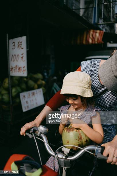 Child sitting in bicycle child seat, drinking coconut water